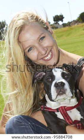 Smiling young adult embracing her Pit Bull puppy - stock photo