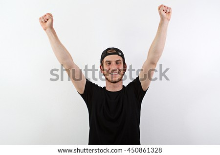 Smiling Young Adult Male in Dark T-Shirt and Baseball Hat Worn Backwards with Arms Raised - stock photo