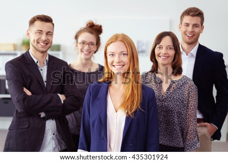 Smiling young adult woman in red hair and blue blazer jacket standing in front of cheerful people in business casual attire - stock photo