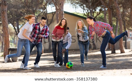 Smiling young adults chasing ball outdoors at sunny day - stock photo