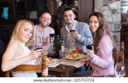 Smiling young adults having dinner in family restaurant - stock photo