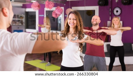 Smiling young adults having group fitness class  - stock photo