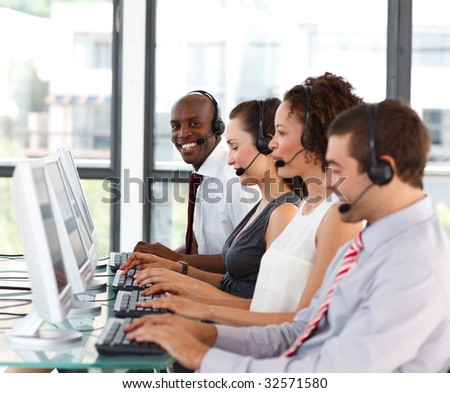 Smiling young African-American businessman in a call center - stock photo