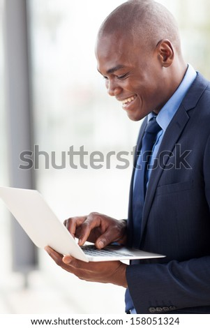 smiling young african american businessman using laptop computer indoors - stock photo