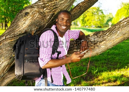 Smiling young african american man in shirt standing near tree and  listens music in a park - stock photo