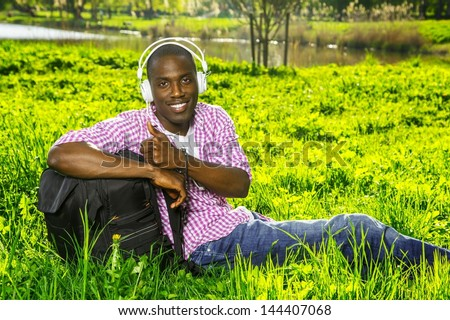 Smiling young african american man  with rucksack listens music in a park - stock photo