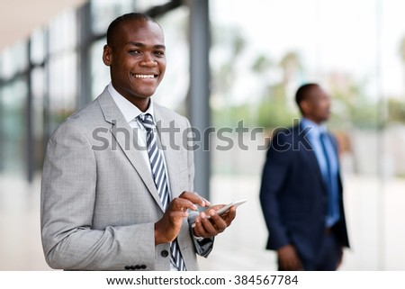 smiling young african businessman reading email on smart phone - stock photo