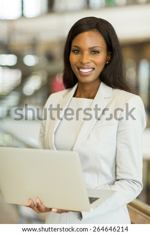 smiling young african businesswoman using laptop computer indoors