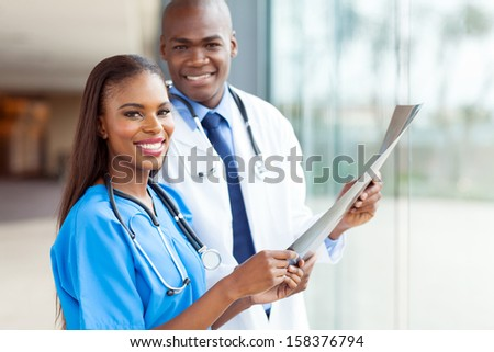 smiling young african medical doctors holding patient's x-ray - stock photo