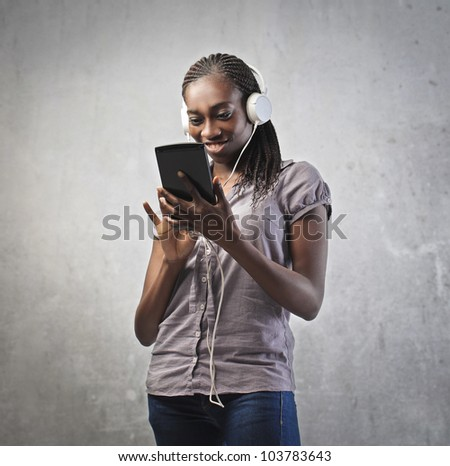 Smiling young african woman using a tablet