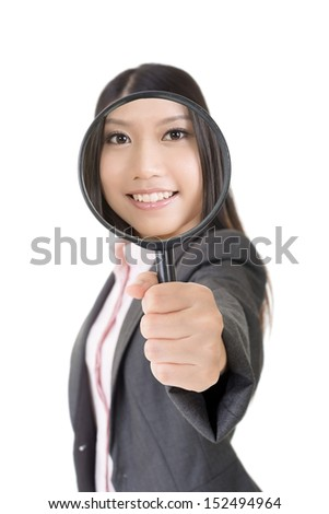 Smiling young asian business woman looking through a magnifying glass. Isolated on the white background. - stock photo