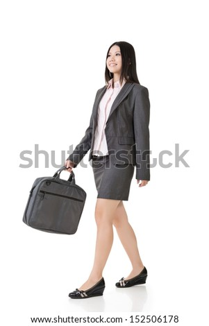 Smiling young asian businesswoman walking with a handbag. Full length. Isolated on the white background.