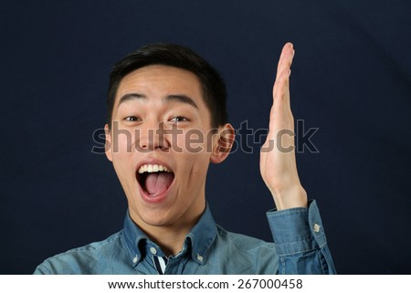 Smiling young Asian man holding his hand upright and looking at camera - stock photo