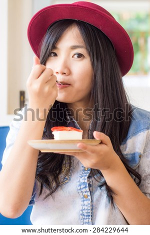 Smiling young asian woman eating cake in bakery shop, Smiling and look so cute - stock photo
