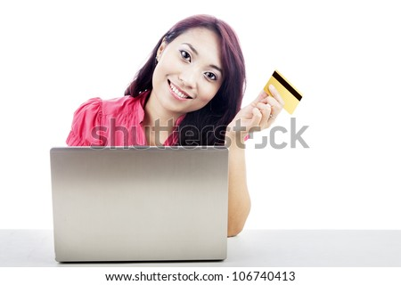 Smiling young asian woman holding a credit card with laptop computer. shot in studio