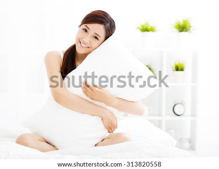 smiling young asian woman  on the bed - stock photo