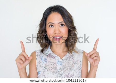 Smiling young Asian woman pointing up with index fingers. Smiling young lady showing something above. Advertisement concept