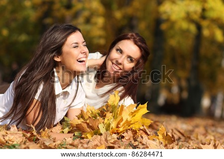 Smiling young attractive women with autumn maple leaves in park at fall outdoors - stock photo