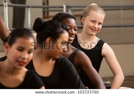 Smiling young ballet student with her classmates - stock photo