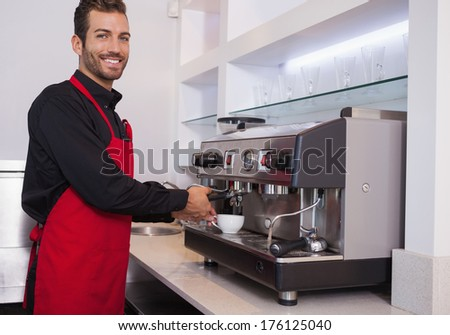 Smiling young barista making cup of coffee in a cafe