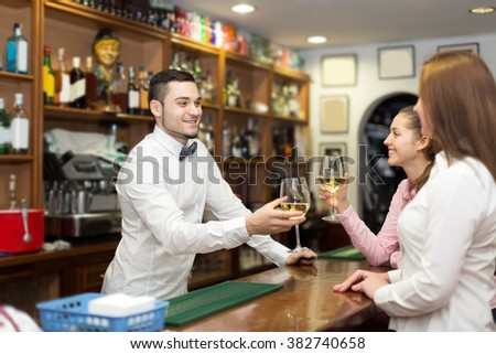 Smiling young bartender and cheerful women at bar - stock photo