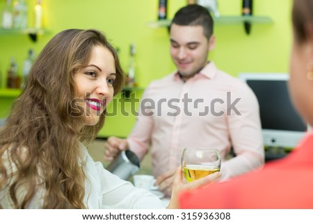 Smiling young bartender and two beautiful girls with wine glasses in hands at bar. Focus on girl  - stock photo