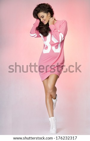 Smiling young beautiful brunette woman posing in studio wearing fashionable pink dress.