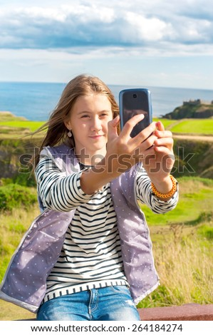 Smiling young beautiful girl taking picture by smartphone in Scotland Aberdeen and Grampian Highlands. Traveling. Summertime outdoors. - stock photo