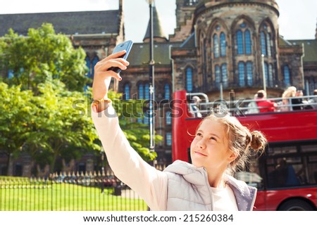 Smiling young beautiful girl taking selfie in Glasgow historical place. Traveling. Summer outdoors. - stock photo