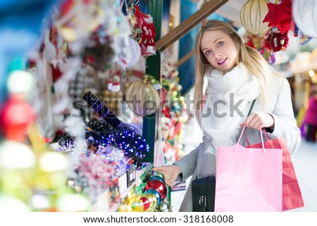 Smiling young beautiful woman choosing Christmas decoration at market