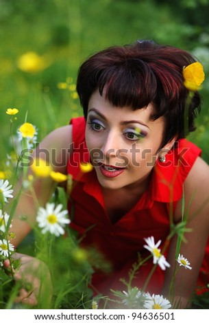 Smiling young beautiful woman laying on green grass