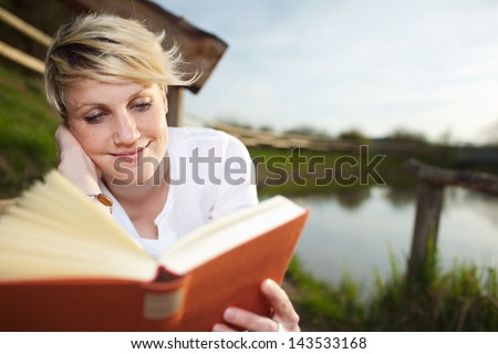 Smiling young beautiful woman reading a book by the country lake - stock photo
