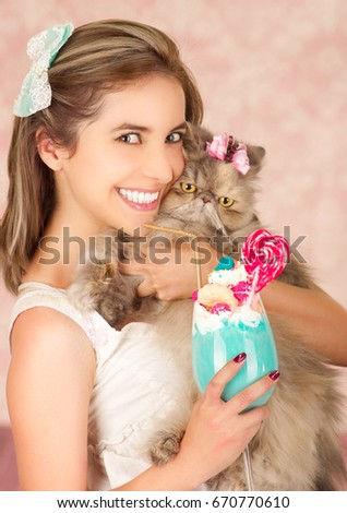 Smiling young beautiful woman, wearing a hair bow, holding a tasty blue milk shake in studio fashion, with a heart candy, plastic straw on a milk foam on top, hugging her cat, in a pink background
