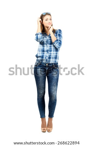 Smiling young beauty scratching head looking at camera. Full body length portrait isolated over white background.  - stock photo