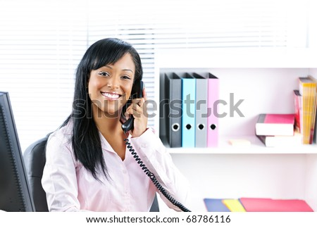 Smiling young black business woman on phone at desk in office - stock photo