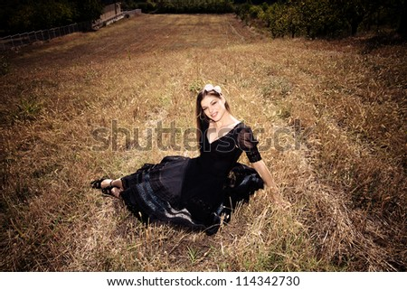 smiling young blond woman in elegant black dress sit in autumn field - stock photo