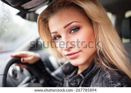 Smiling young blond woman sat in motor car. - stock photo