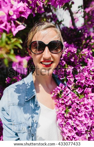 Smiling young blond woman wearing sunglasses and jeans jacket in sun surrounded by purple flower blooms on tree
