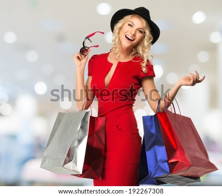 Smiling young blond woman with shopping bags in shop interior  - stock photo