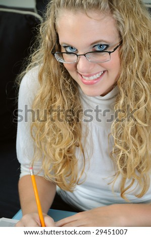 Smiling young blonde woman holding pencil - stock photo