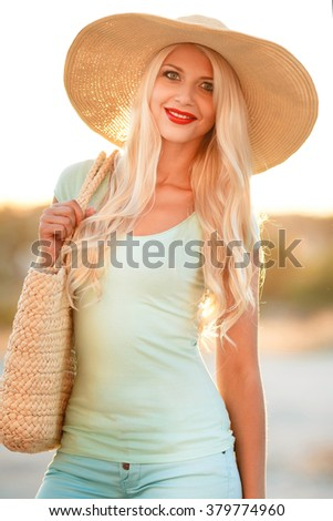 smiling young blonde woman in straw hat in sunset light. Young and beautiful woman wearing a hat in sunset light looking far away. girl in happy summer sun - stock photo