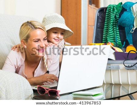Smiling young blonde woman with cute little daughter planning vacation at home