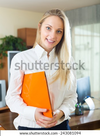 Smiling young blonde woman with documents working in office room - stock photo
