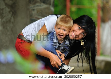Smiling young blue-eyed brunette hugging his red-haired little boy and helps him tie the laces on sneakers