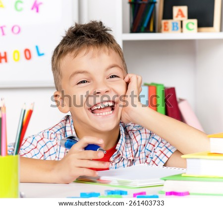 Smiling young boy doing homework at the table