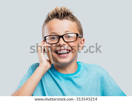 Smiling young boy having a phone call with his touch screen smart phone - stock photo
