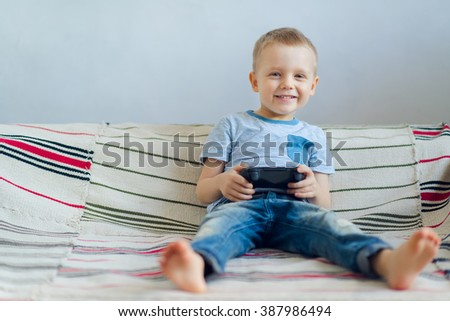 Smiling young boy playing with playstation at home - stock photo