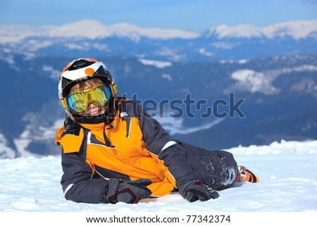 Smiling young boy skier on snowy mountain with helmet and face mask or goggles, - stock photo