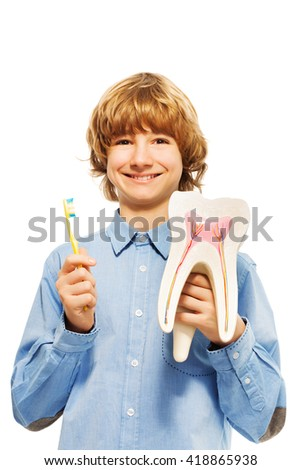 Smiling young boy with tooth model and toothbrush - stock photo