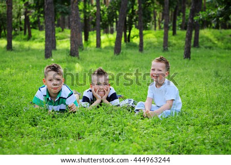 Smiling young boys lying on green grass and looking to the camera. Three Dreaming adorable brothers lying on grass - stock photo